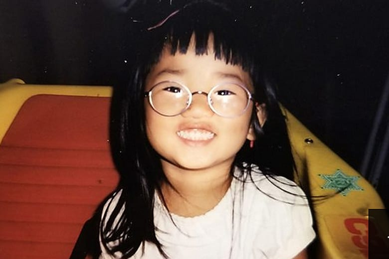 A young Kati smiles with glasses on.