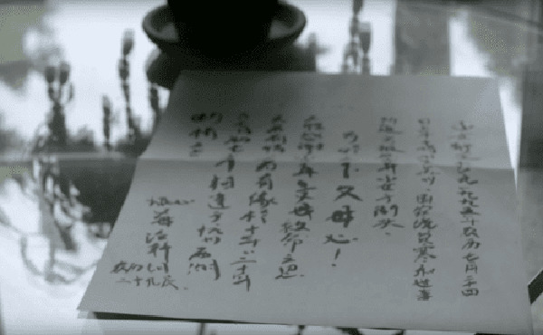 A letter written in Chinese sits on a glass table.