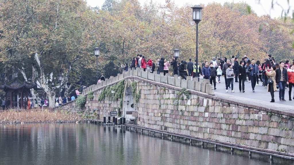 People cross Broken Bridge in China.