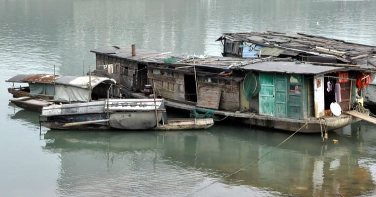 A rundown house boat sits on the water.