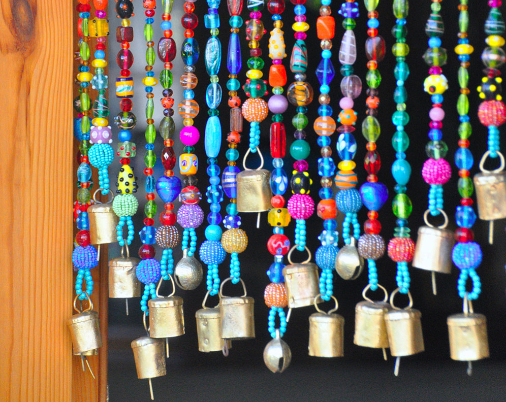A beaded wall curtain has bells on the end.