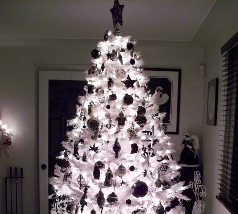 A white tree with black decorations appears to be in the negative.