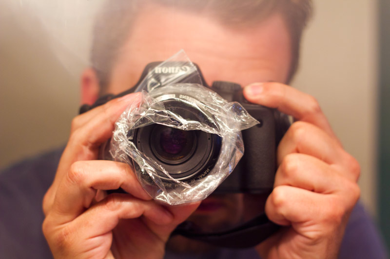 A man uses a camera lined with plastic wrap.