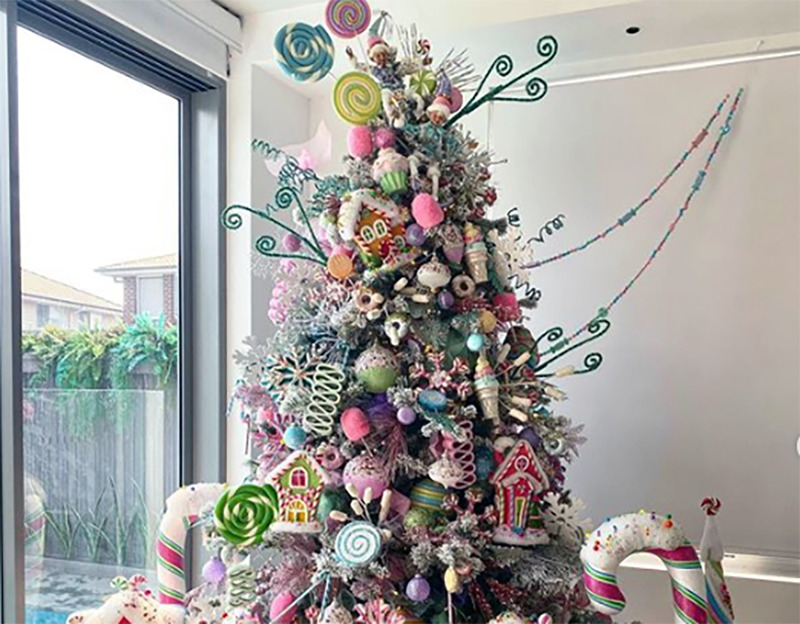 A Christmas tree is covered is candy decor.