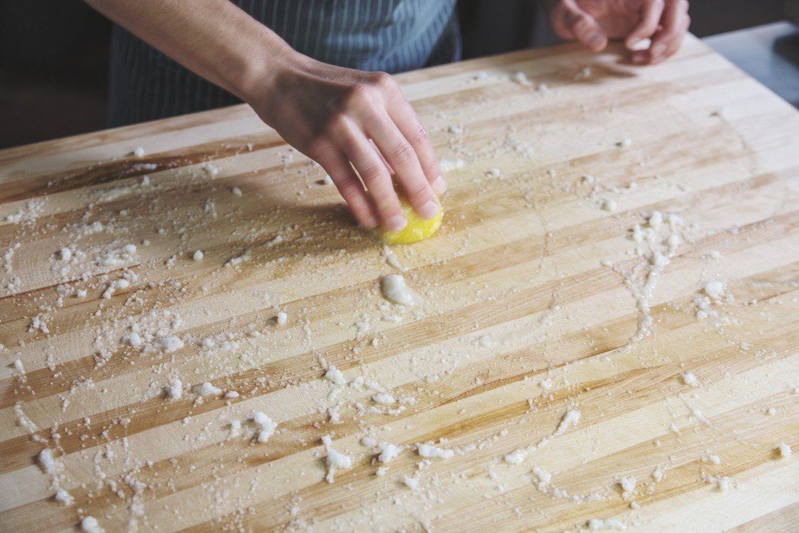 A chef wipes a wooden cutting board with beeswax.