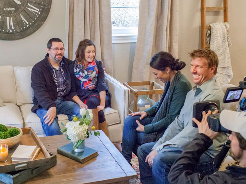 Chip and Joanna Gaines talk to clients while on camera.