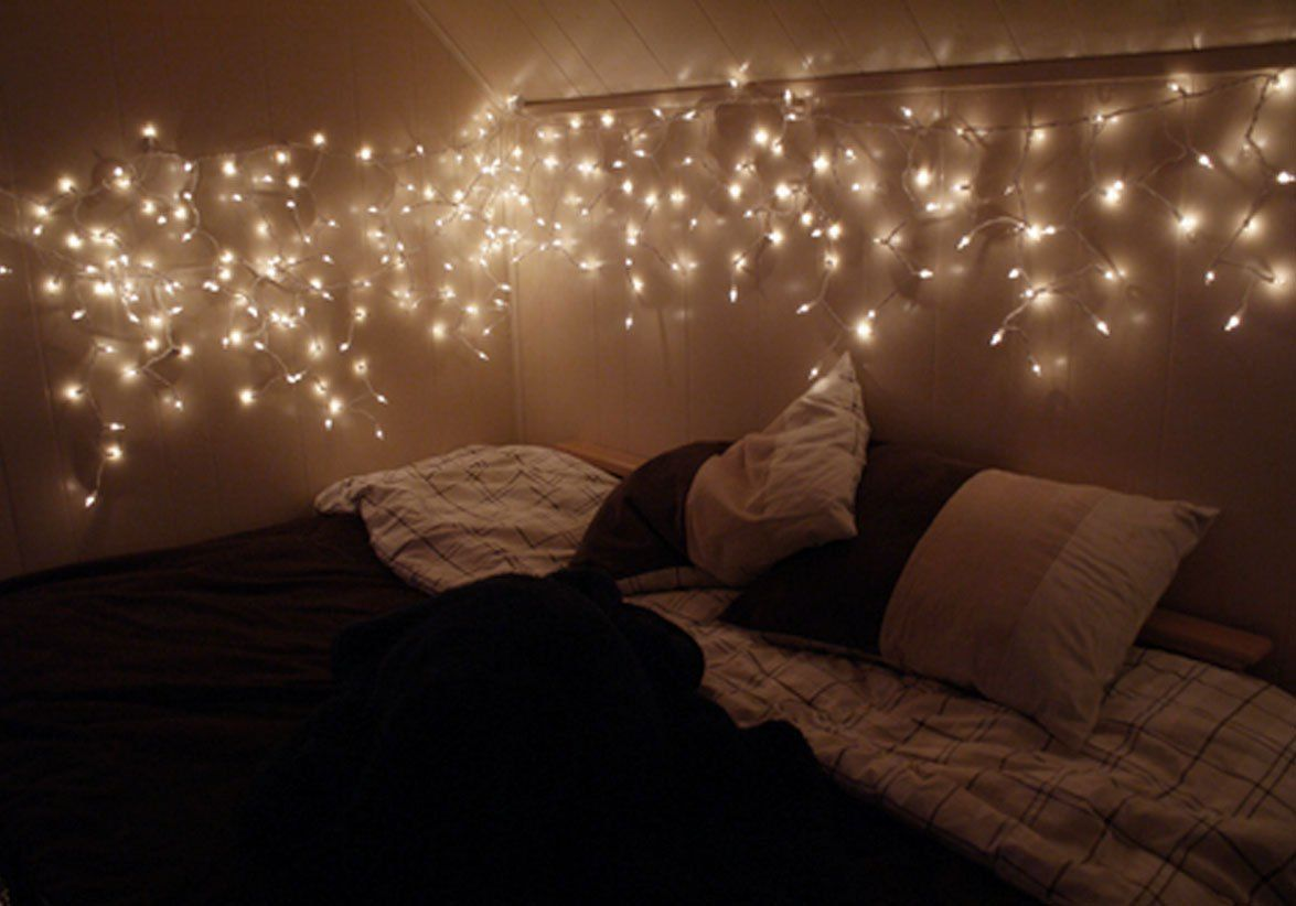 Fairy lights are hung above a bed in a bedroom.