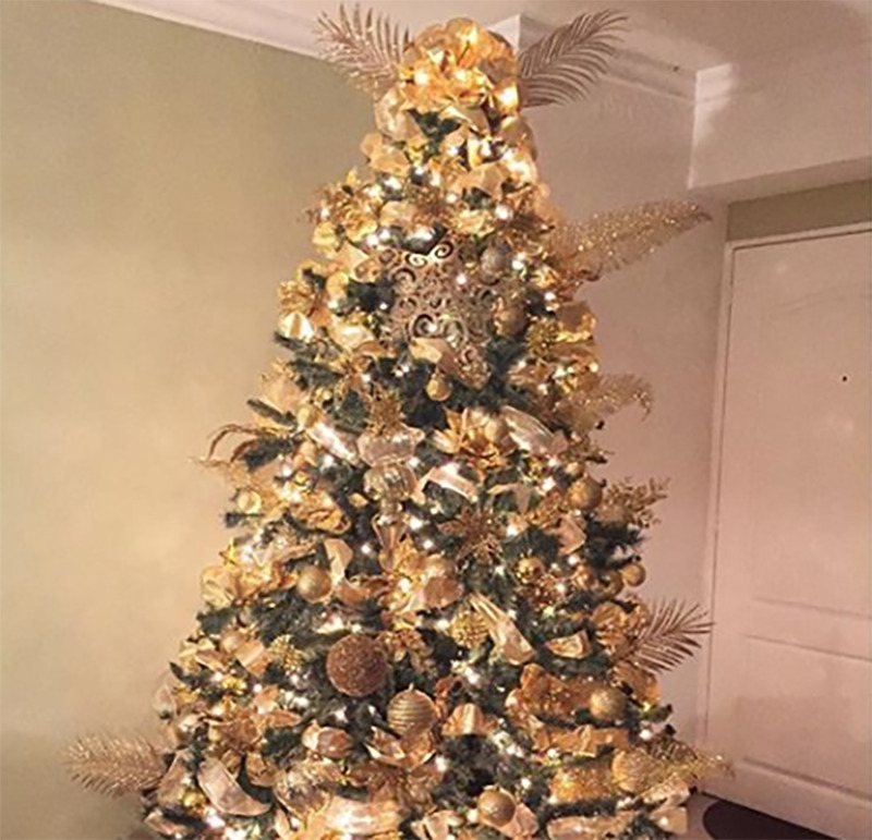 A Christmas tree is covered in all-gold decorations.