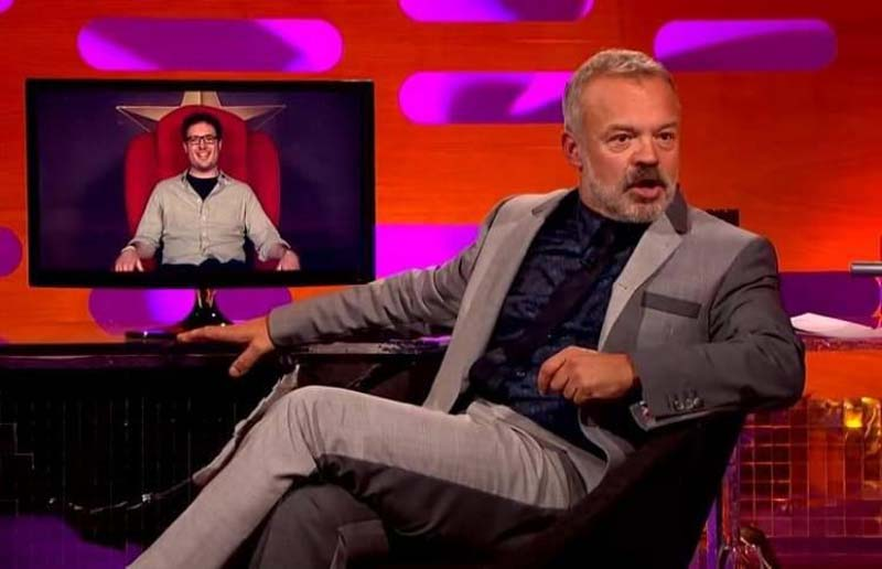 Graham Norton watches on a television screen the man in the big red chair.