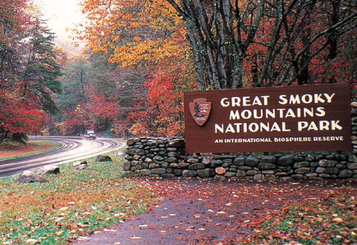 A sign for a national park is near the road underneath autumn trees.