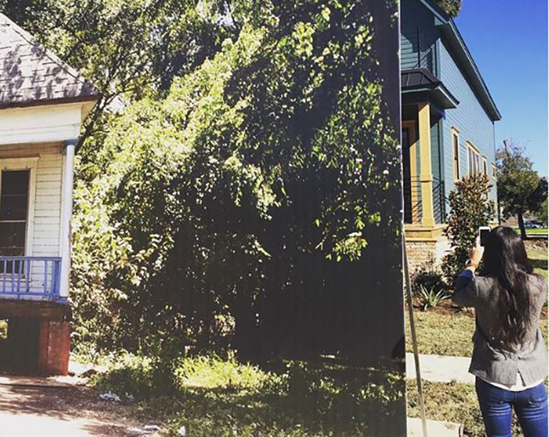 Joanna Gaines takes a picture of a home covered by a large poster.