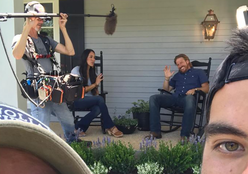 People take a selfie while a production team films Fixer Upper.