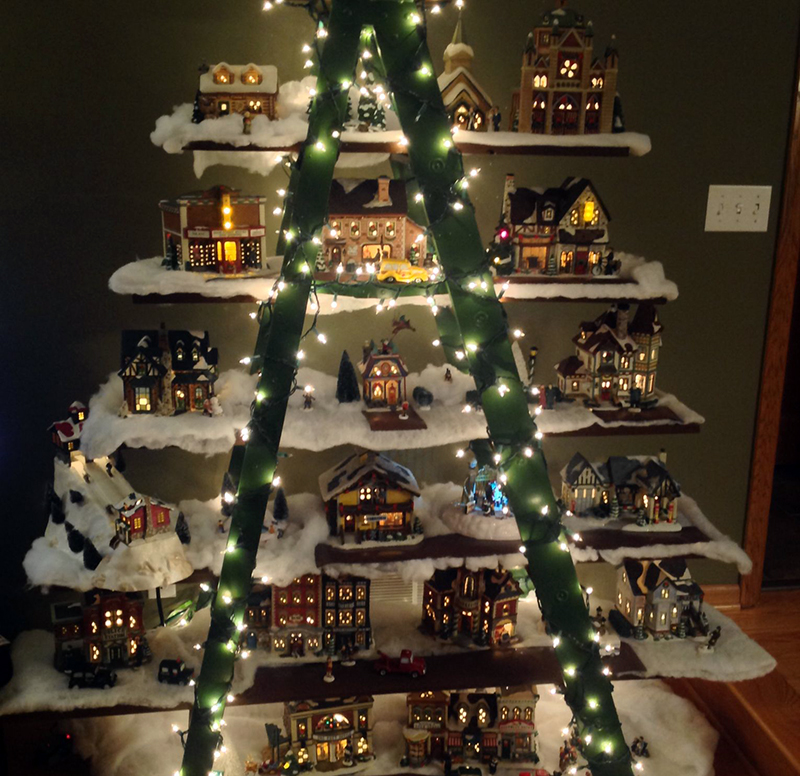 A ladder is made into a Christmas tree with layers of miniature Christmas towns.