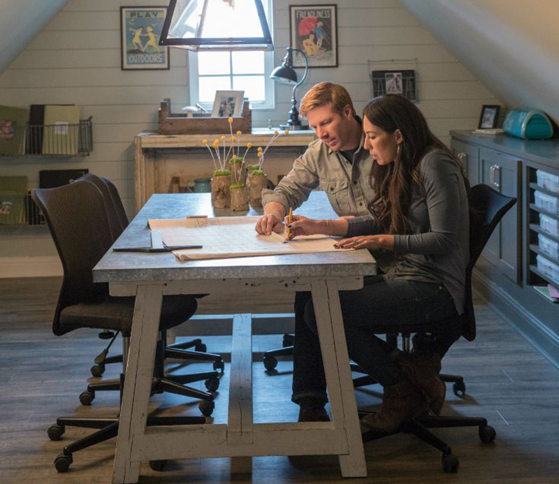 Chip and Joanna Gaines look over a blueprint on the show