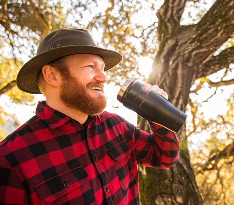 A man smiles while holding up a thermos.