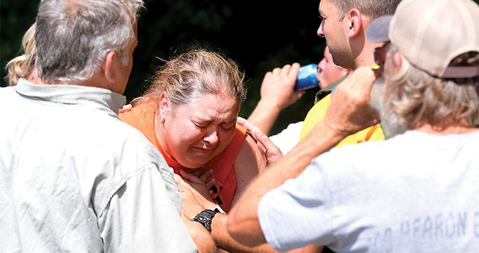 Austin's mother cries while surrounded by supporters.