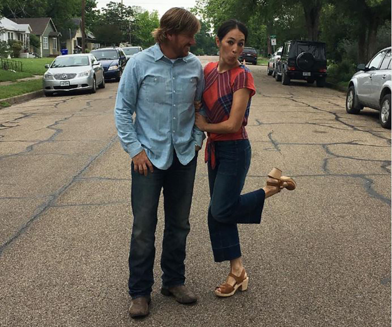 Chip and Joanna Gaines pose in the middle of the street.