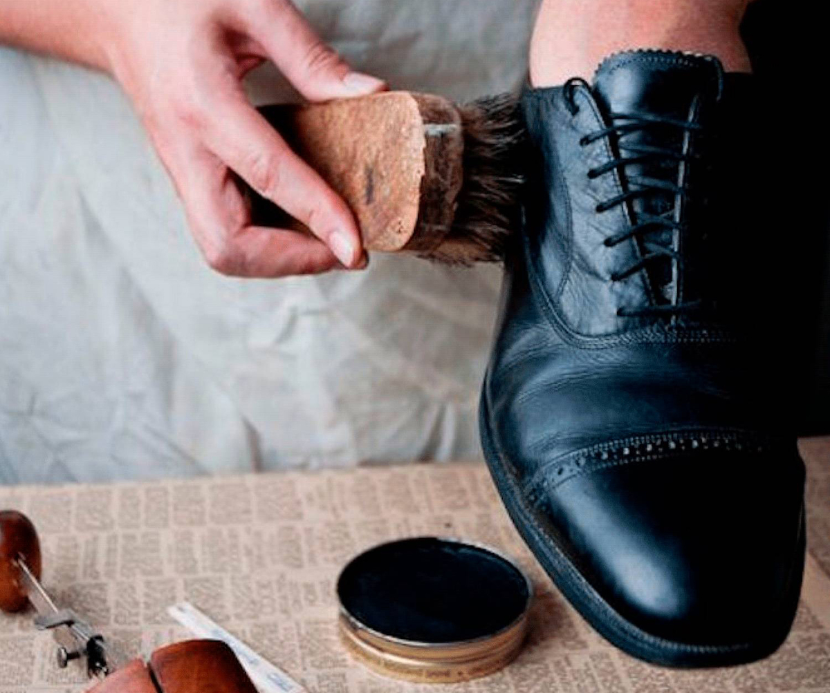 A man polishes his black leather shoe.