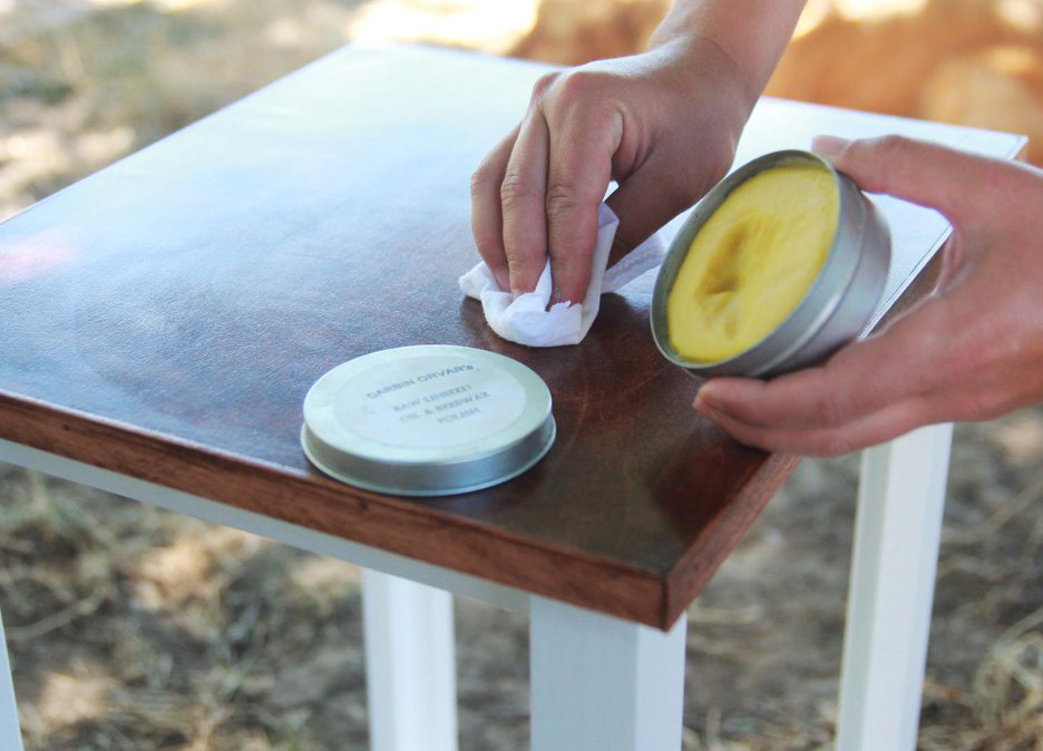 A woman polishes a wooden table with a mixture of linseed oil and beeswax.