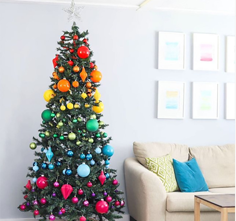 A Christmas tree is decorated with ornaments the colors of the rainbow.
