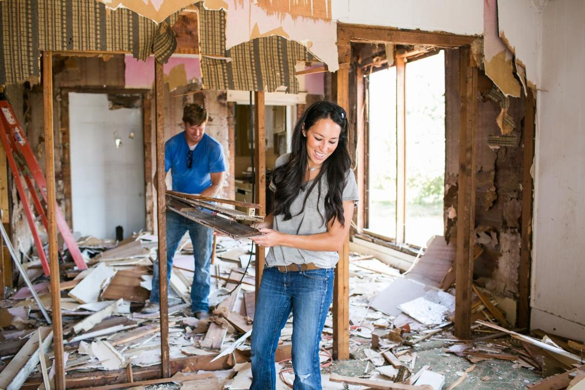 Joanna Gaines helps her husband carry wood through a home during renovation.