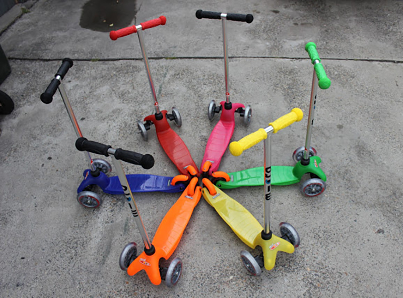 Six micro scooters in various colors are placed in a circle.