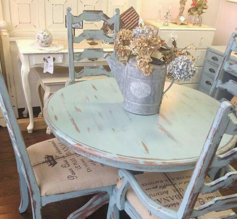 A mint kitchen table is distressed with a watering can of flowers on it.