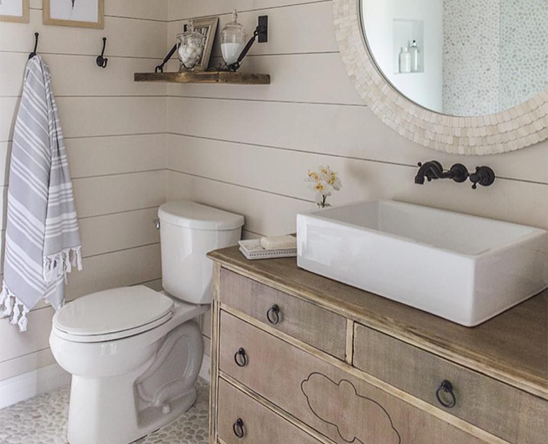 A bathroom is garnished with shiplap wooden walls.