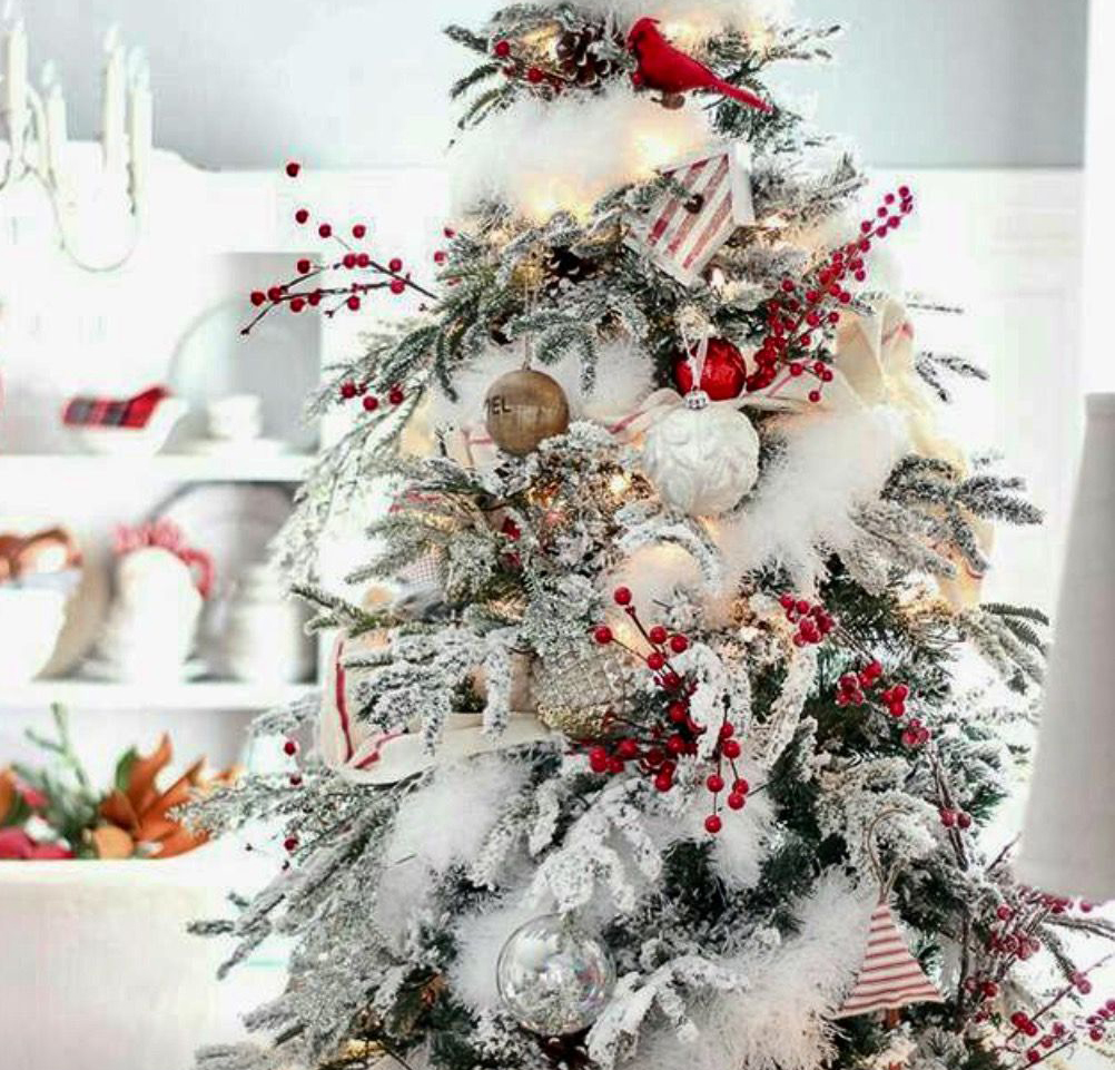 A Christmas tree has white decorations and red berries.