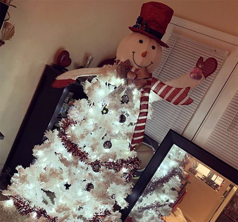 A white Christmas tree is decorated to look like a snowman.
