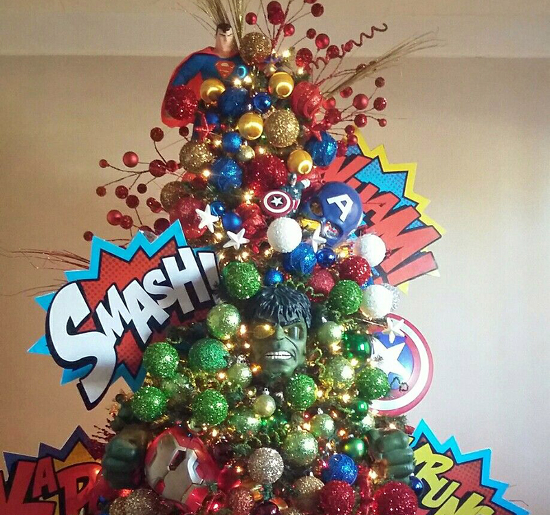 A Christmas tree is covered in superhero decorations.