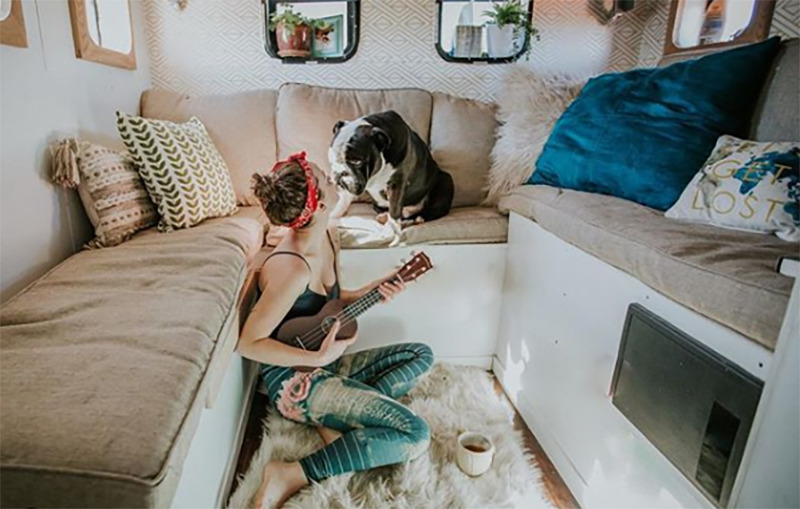 Kourtney sits on the living room floor and plays ukelele for her bulldog.