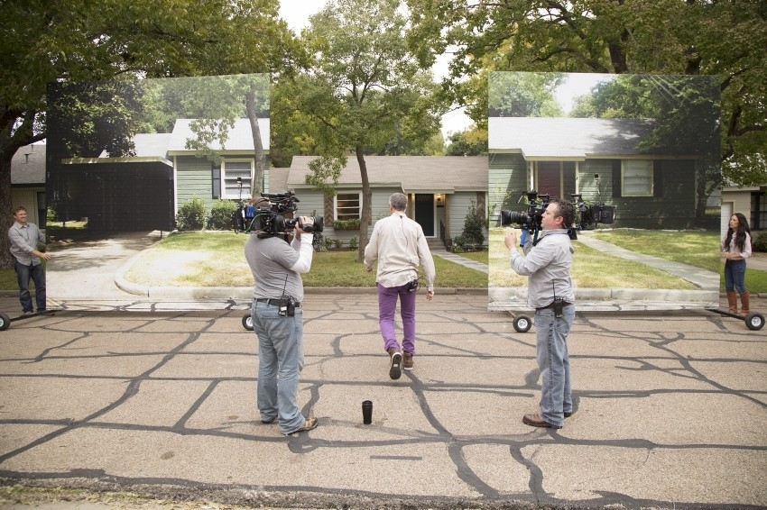 A participant walks toward a revealed home on the show 'Fixer Upper.'