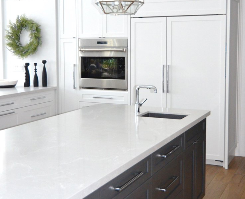 A white kitchen features a counter, oven, and wreath on the wall.