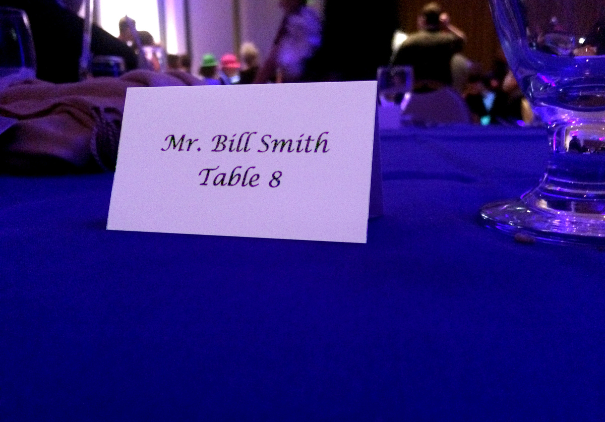 A name tag reserves table eight for Mr. Bill Smith.