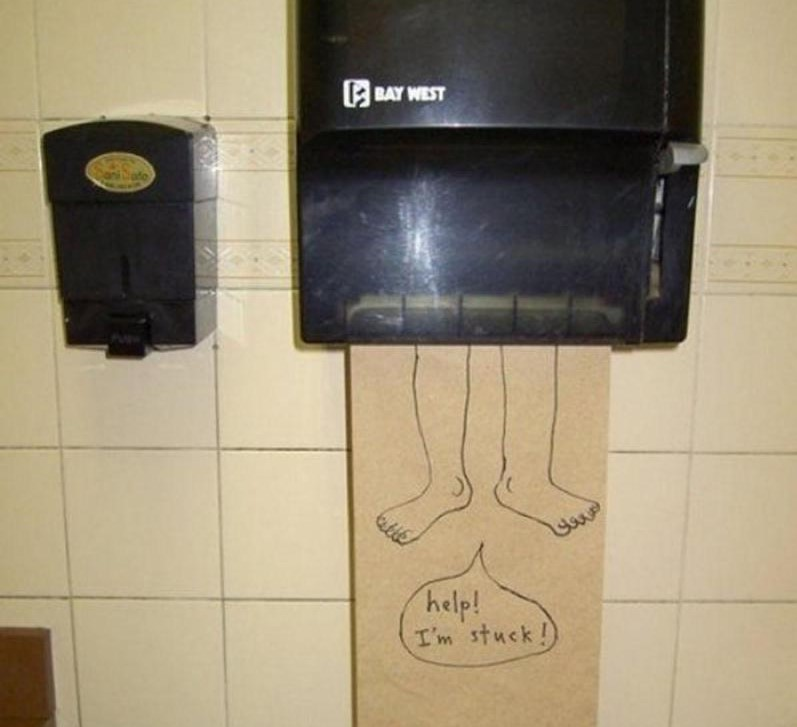 A paper towel with a drawing of legs hangs out of a dispenser.