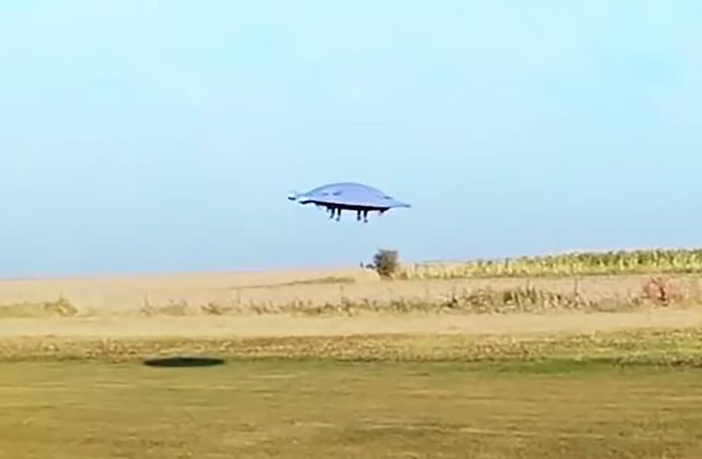 Saucer over grass field