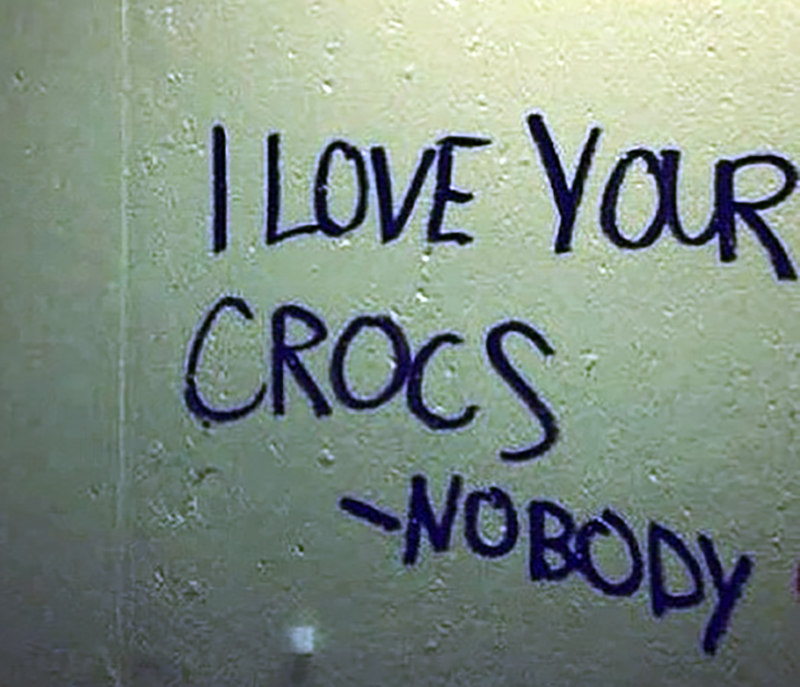 A bathroom note implies that no one loves crocs.