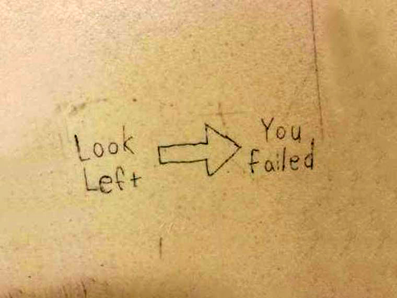 A bathroom wall says to look left but an arrow points to the right.