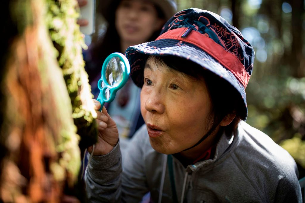 A woman looks through a magnifying glass.