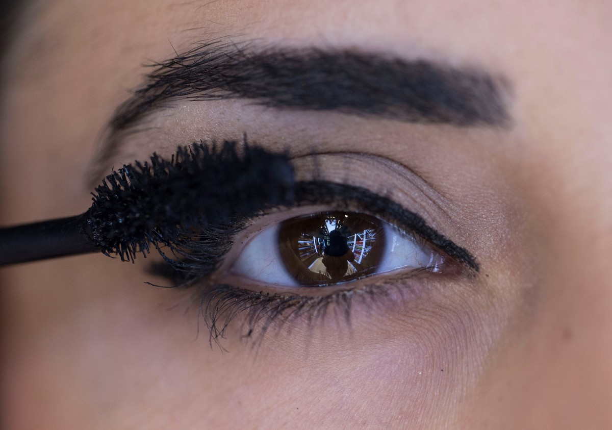 Close-up shows a woman with brown eyes applying mascara.