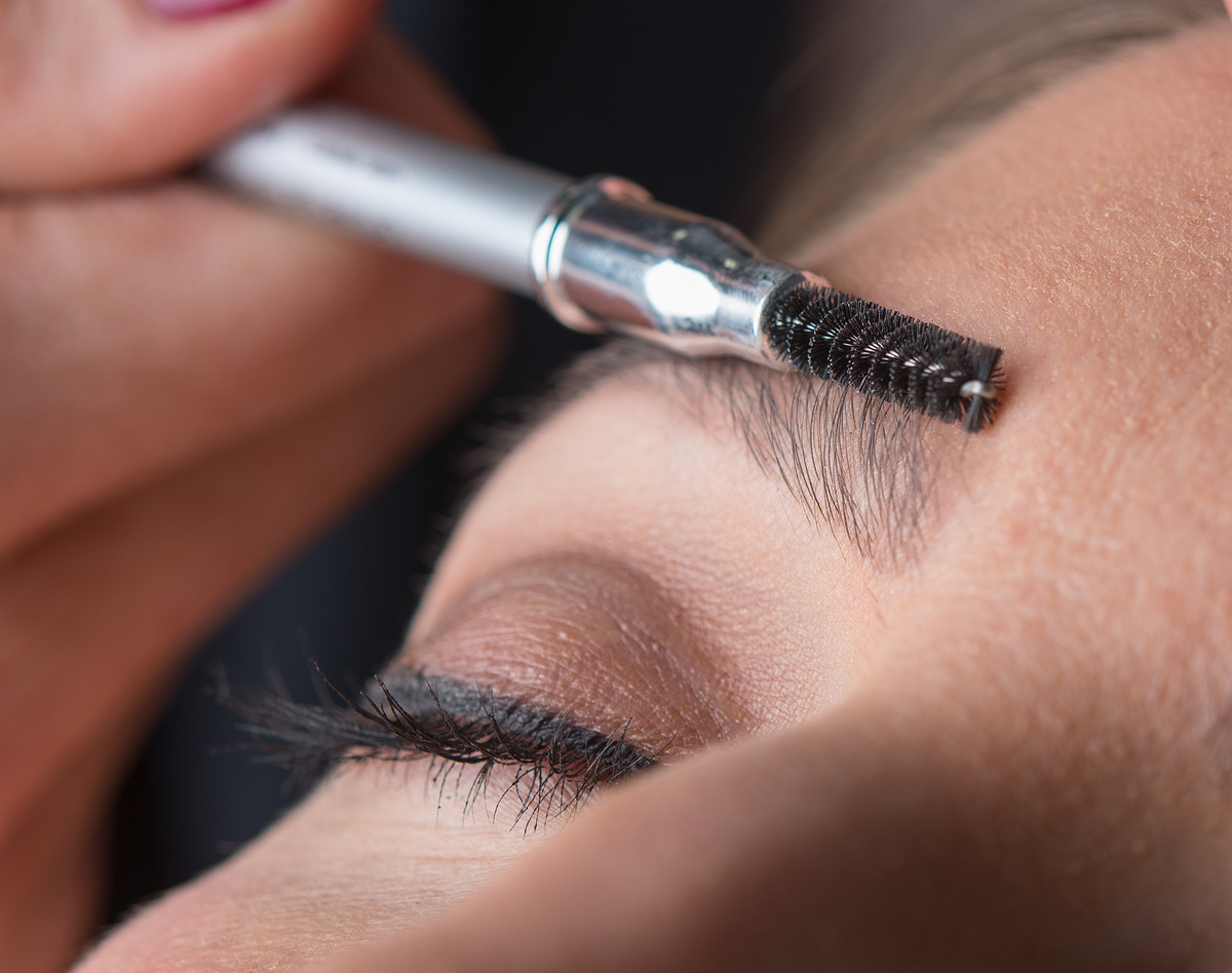 A makeup artist straightens a woman's eyebrows with a small brush.