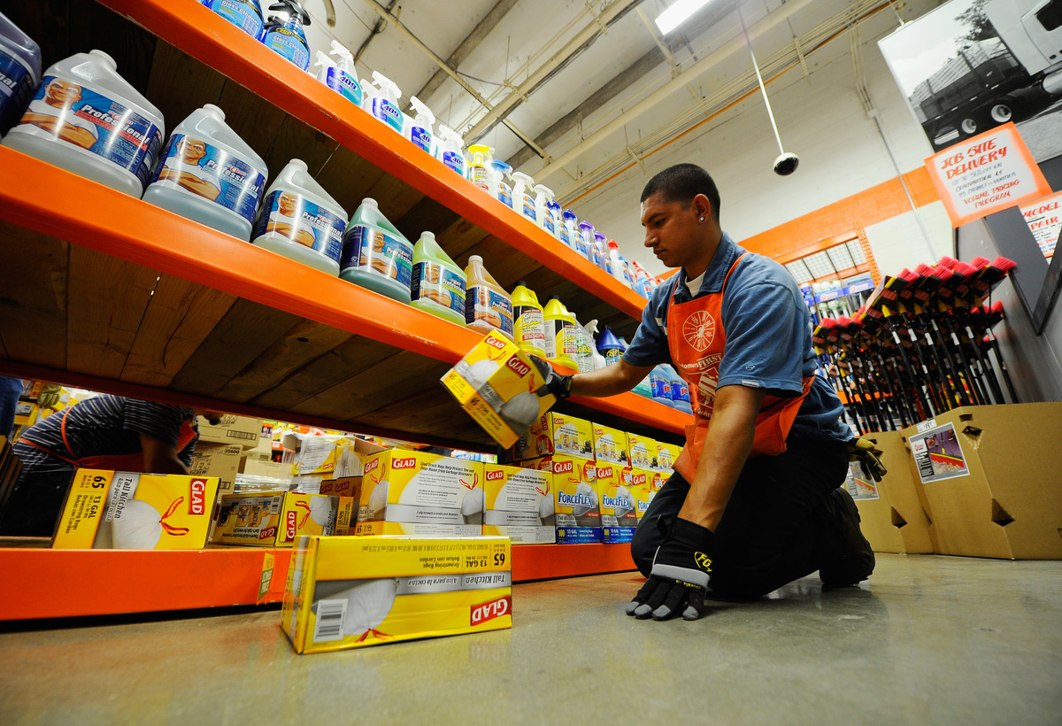 An employee stacks trash bags in Home Depot.