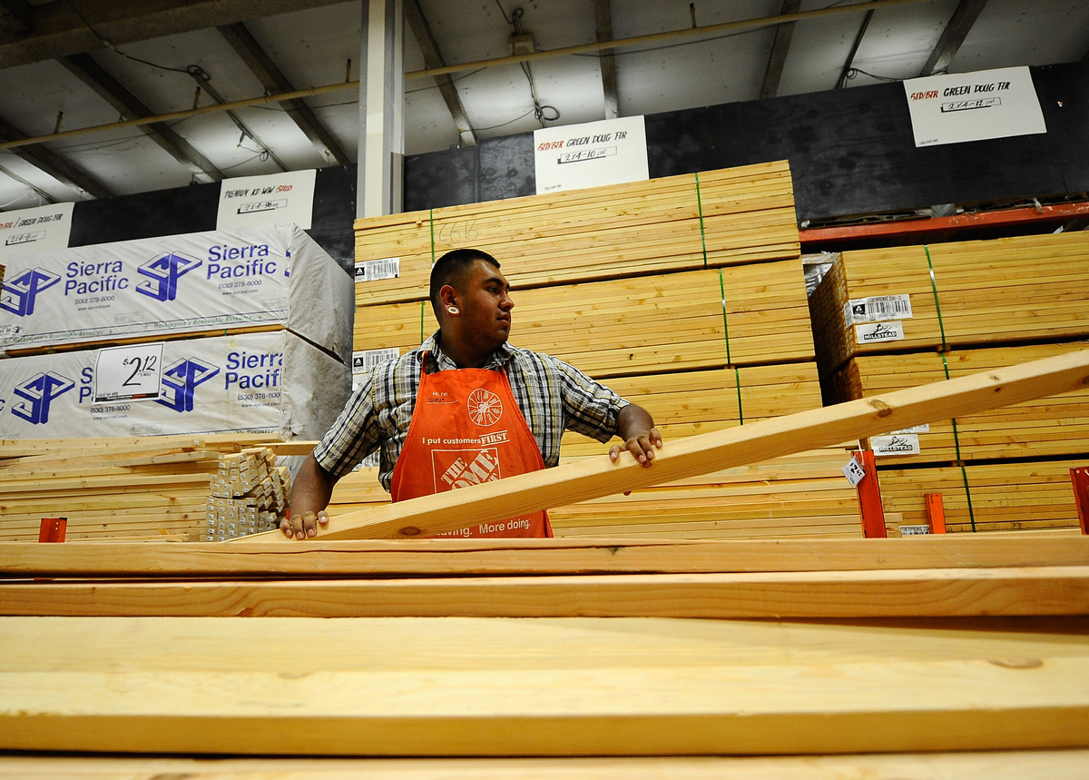 A Home Depot employee stacks lumber.