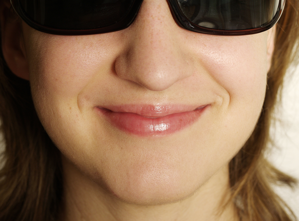A close-up shows a woman's square-shaped jawline.