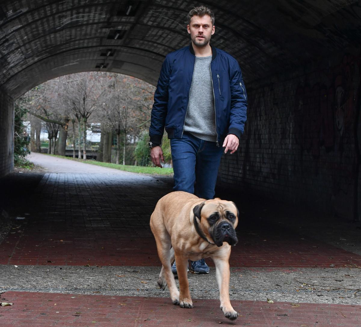 Actor Jens Atzorn walks with a bullmastiff through a tunnel.
