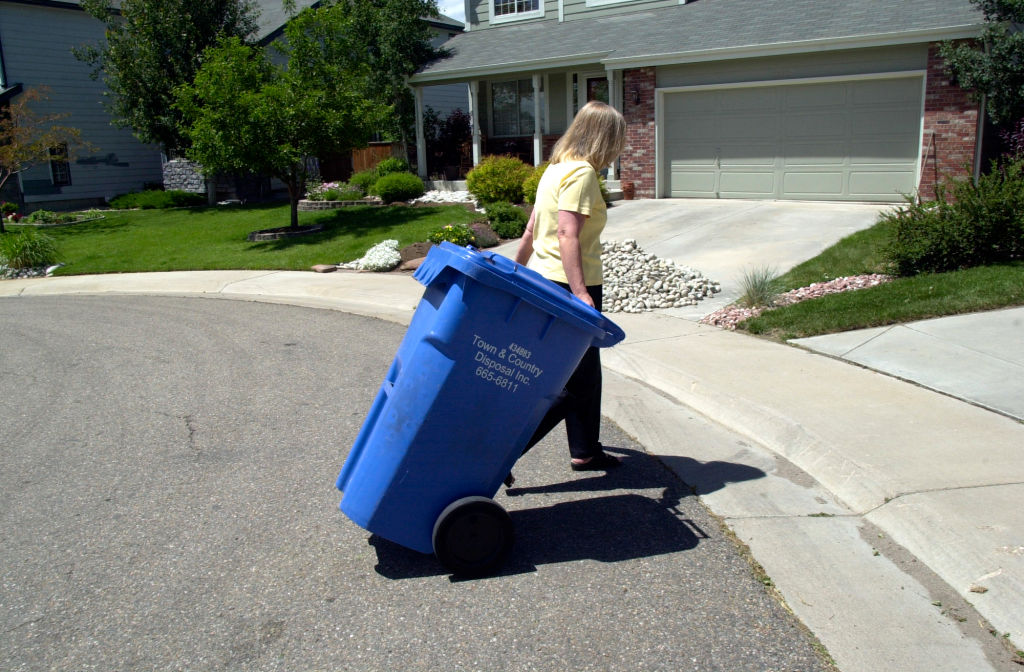 A woman brings in a trash bin.