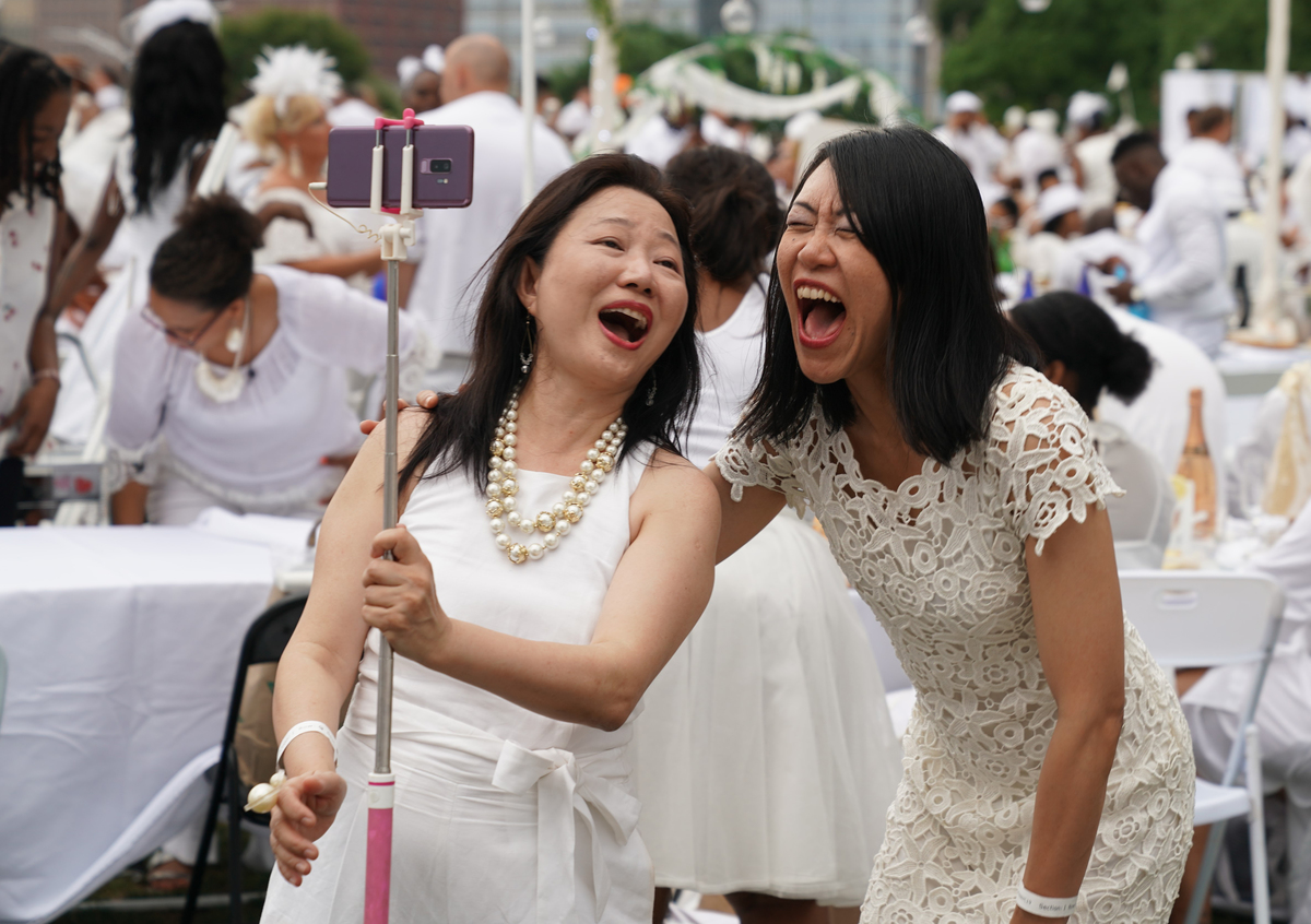 Women laugh together as they take a selfie.