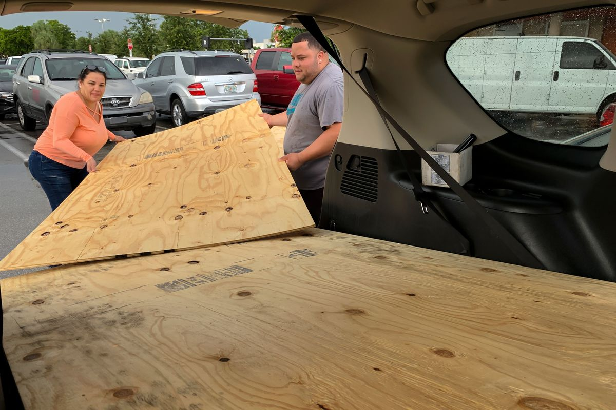 Customers load large plants of wood into the trunk of their car.