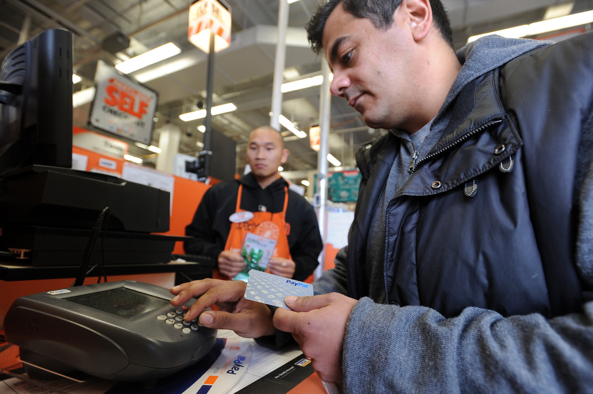 An employee enters digits on his card to pay at Home Depot.